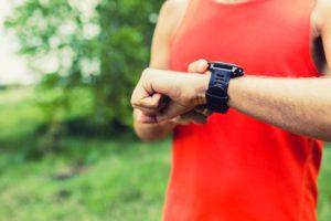 man running and checking sport smart watch PWATC