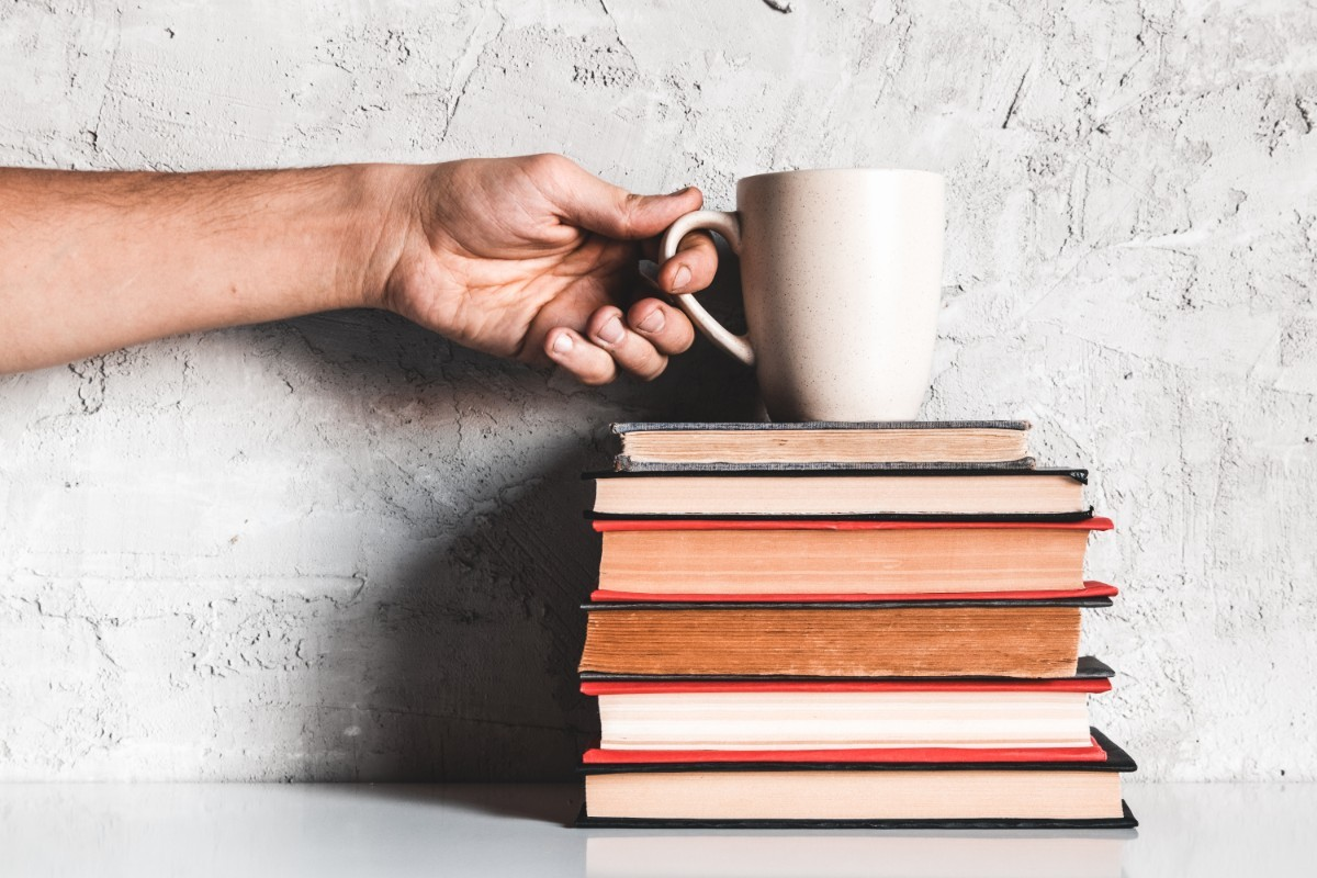 a-man-takes-coffee-from-a-stack-of-books-EECUP5N