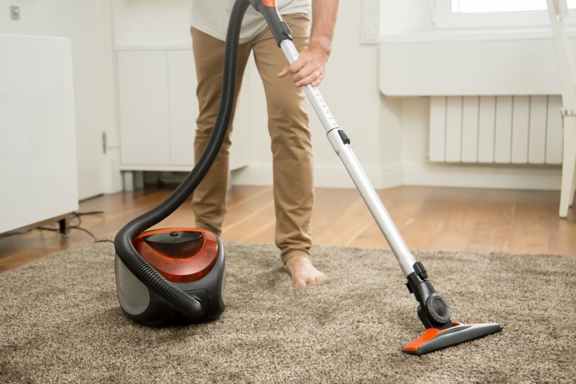 close up of man vacuum cleaning the carpet PHTXG