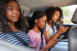 teenage children using digital devices on family PULYAN