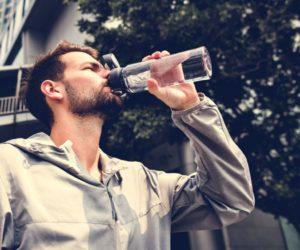man drinking out of a water bottle PNRWJH