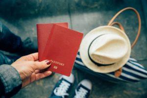 woman holding passports close up at airport PKEBEU