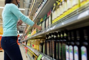 woman choosing olive oil at supermarket or grocery PVESVVD