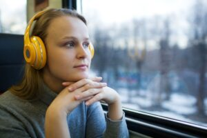 woman traveling by train with favorite music HFMD