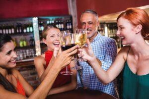 friends toasting wine glass in night club afy