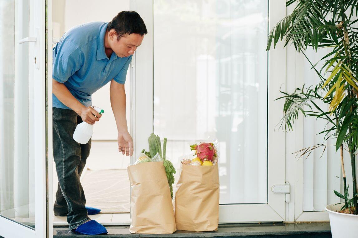 man-spraying-delivered-grocery-packages-tv65ekk-1