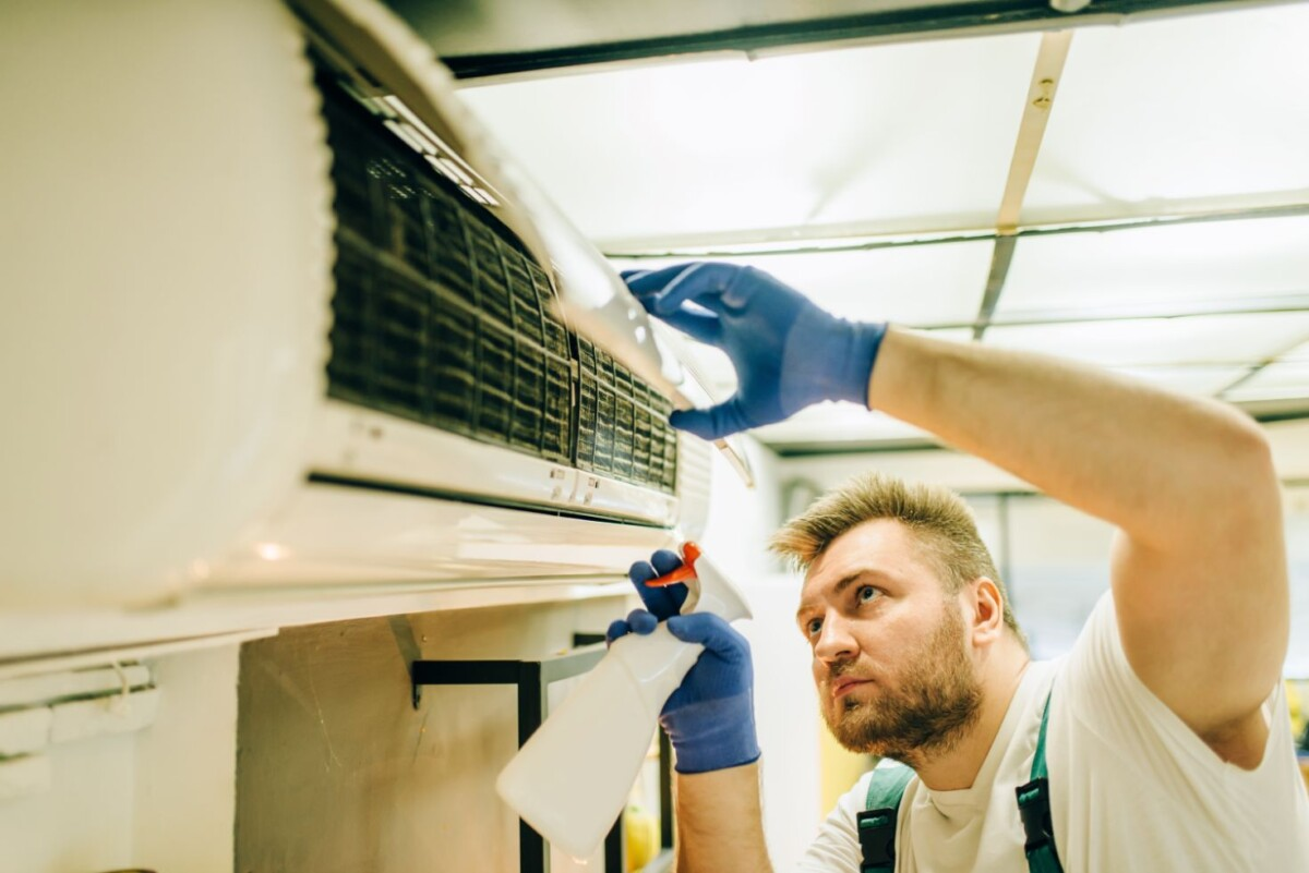 repairman in uniform cleans the air conditioner zhesw