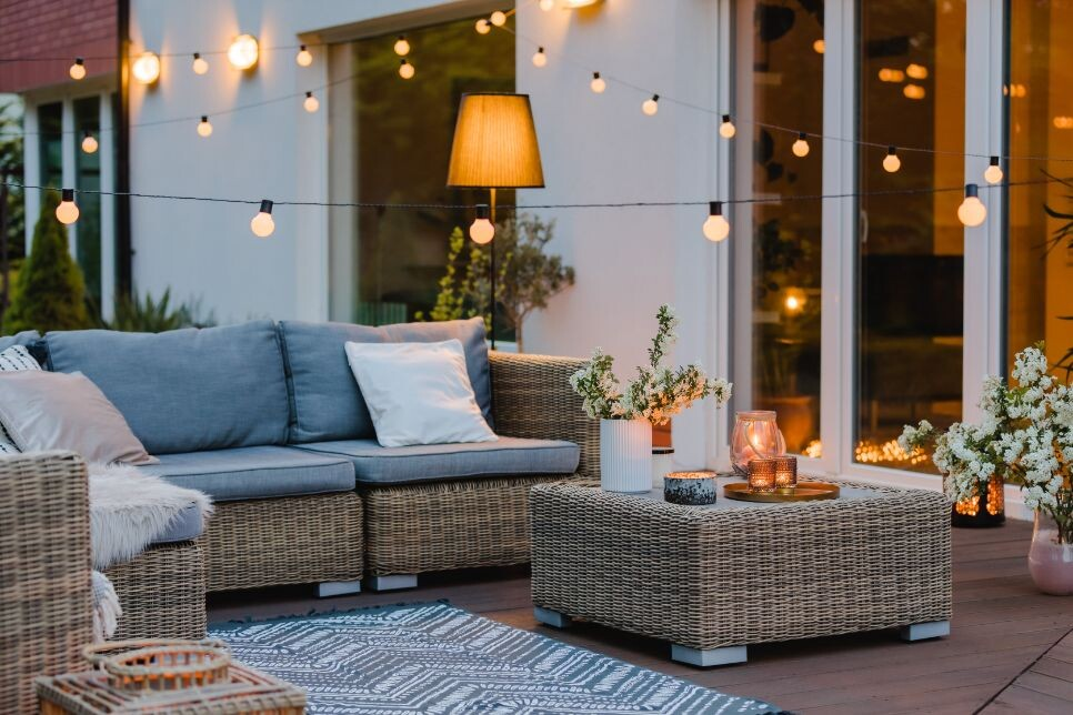 summer with patio with wicker furniture and lights tkdf