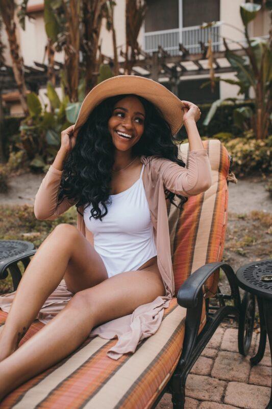 girl holding hat smiling