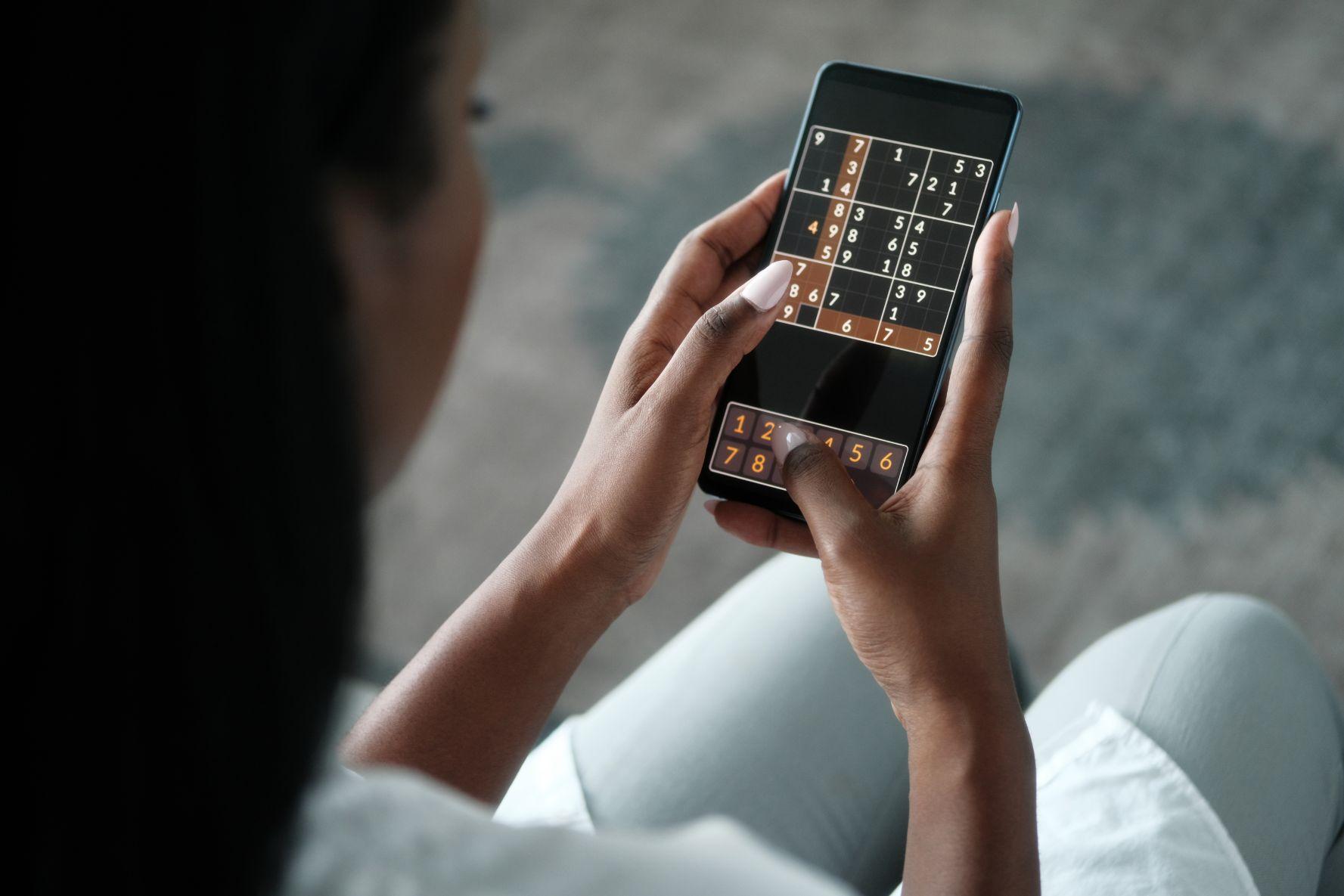 woman playing sudoku for brain training aar
