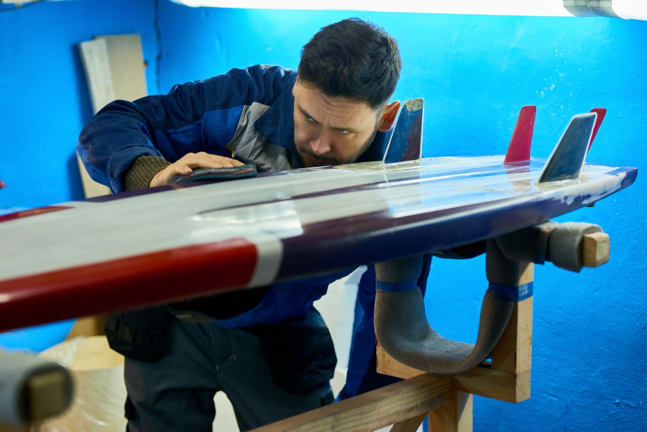 handsome man polishing custom surfing board JHRDAUG