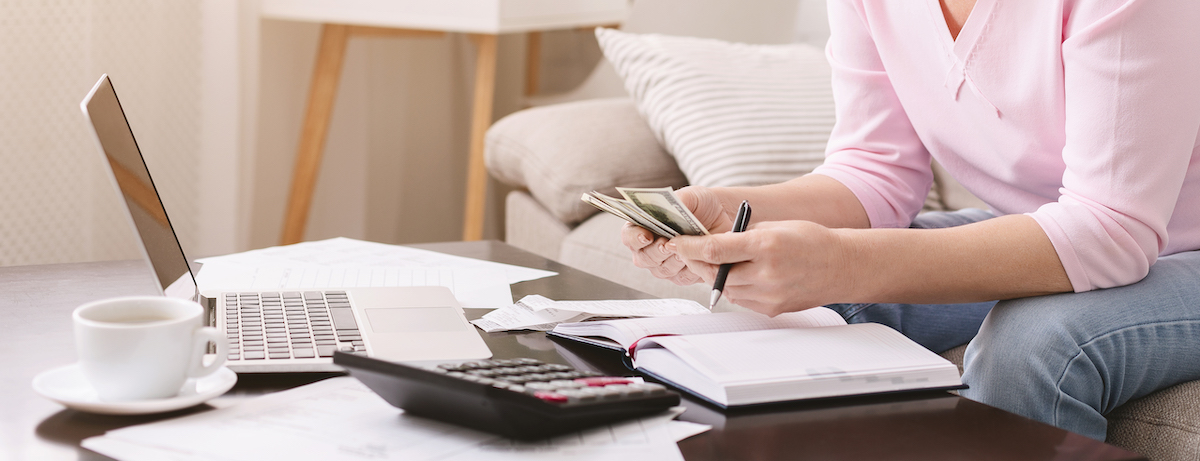 retired woman counting money bills at home