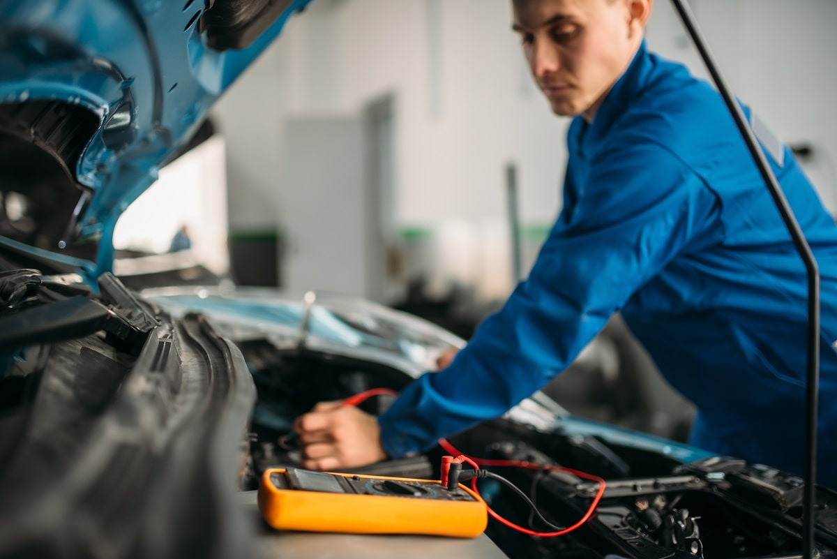 car repairman with multimeter battery inspection