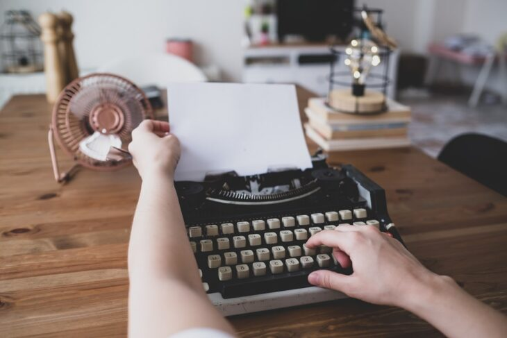 writing a book with old typewriter on wooden table