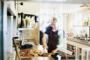 female chef cutting pizza in commercial kitchen PPDWT