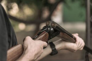 man charging double barreled hunting rifle closeup PNYD