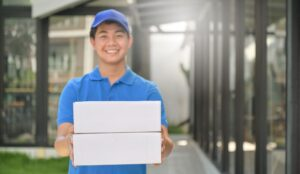 parcel delivery worker holding a box in hand ready HRVWCHZ