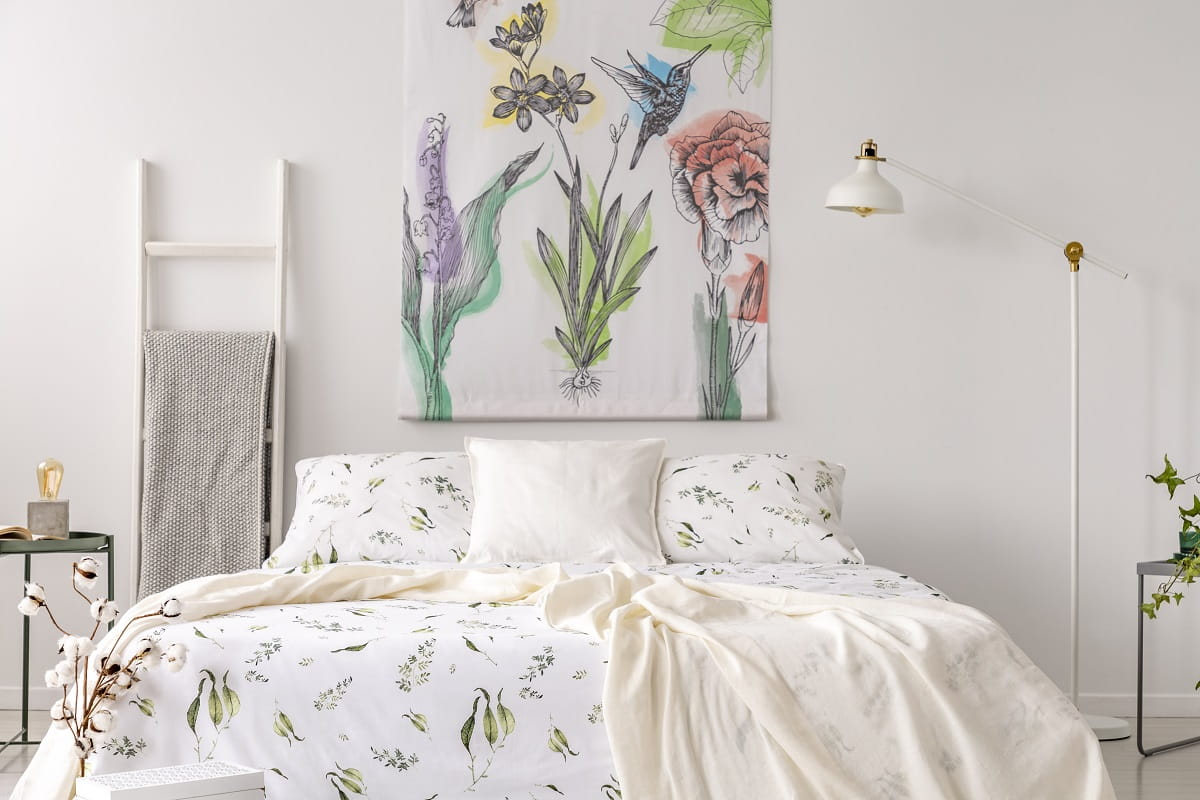 a pastel bedroom interior with a bed dressed in green plants pat