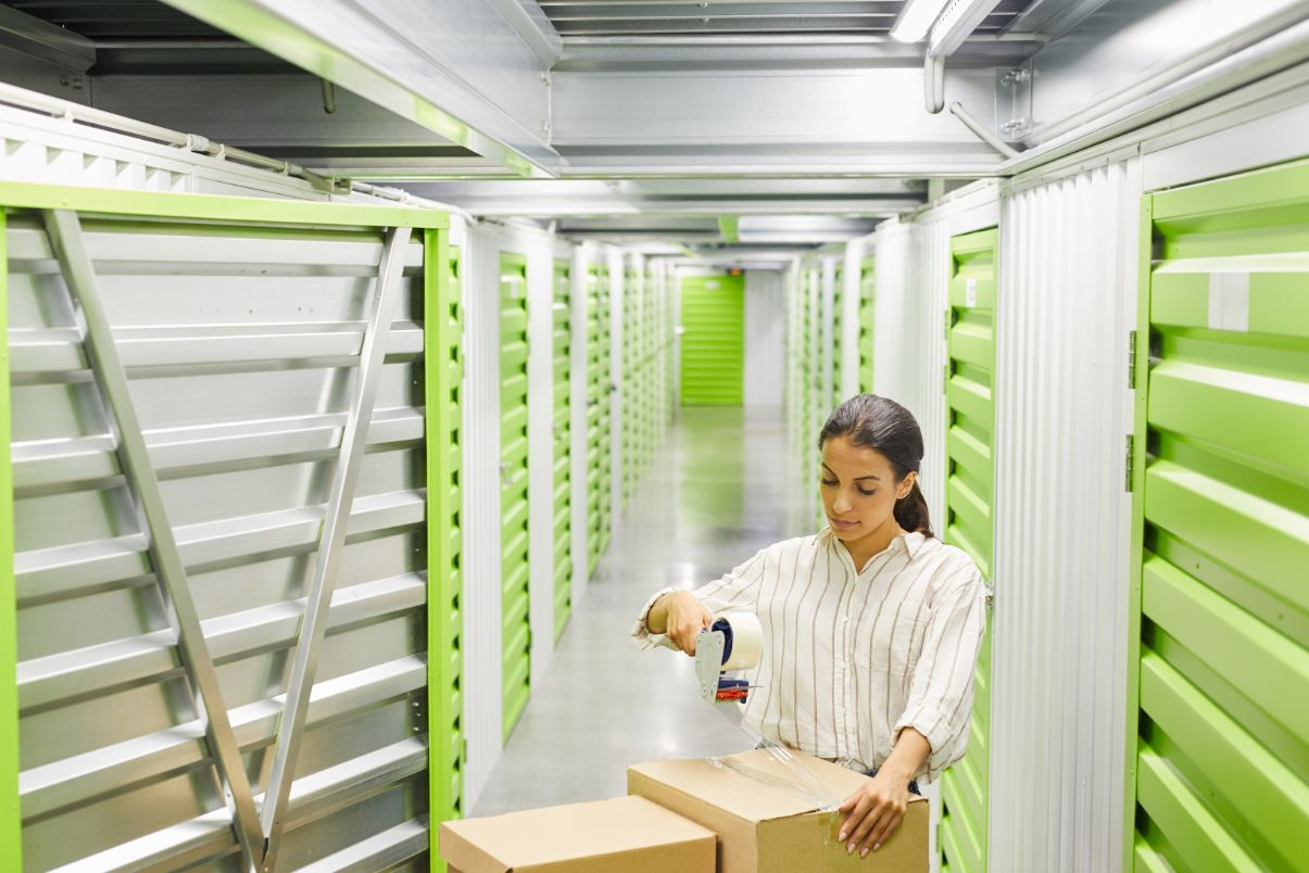 portrait of woman packing boxes in storage unit GBMXN