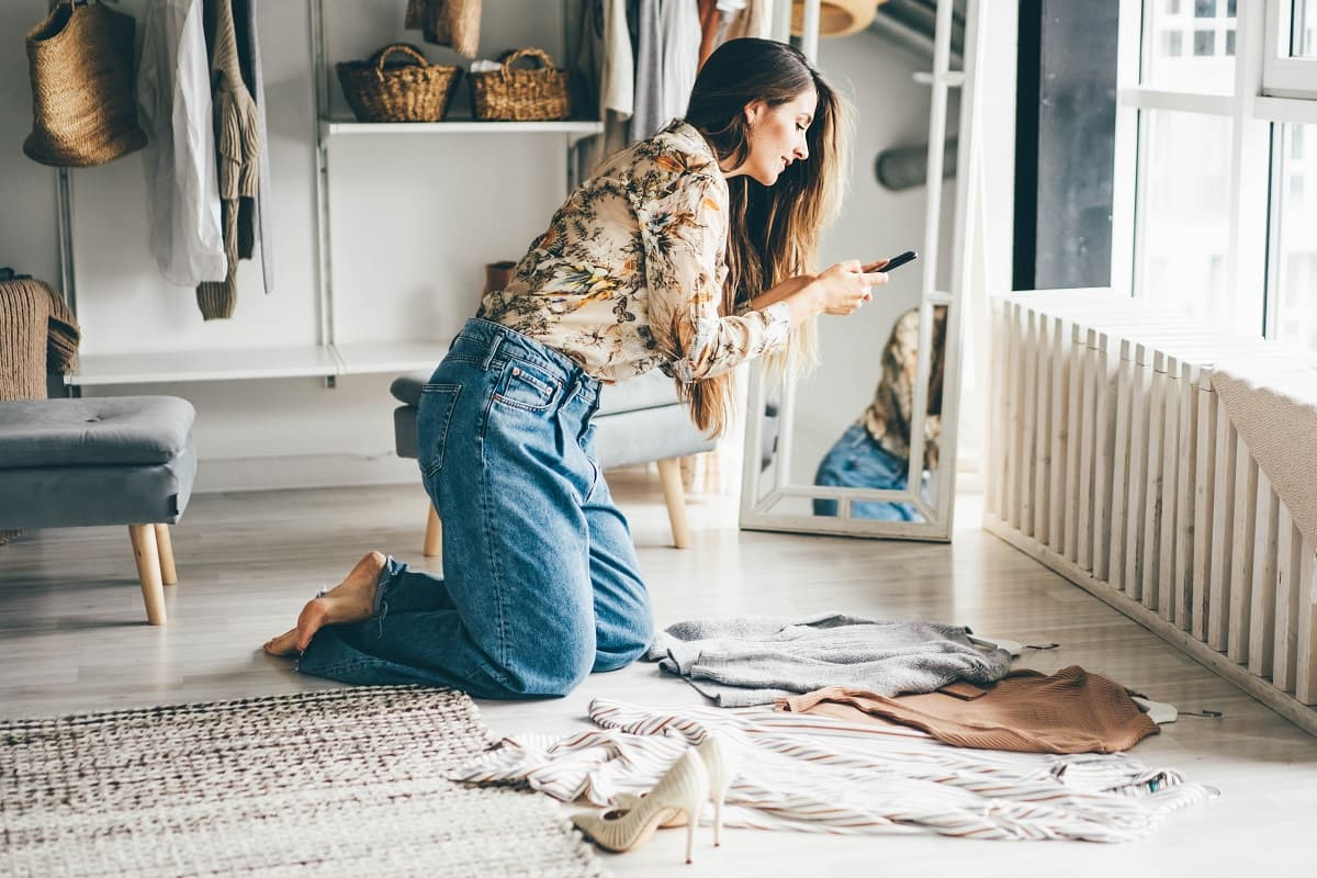 woman holds smartphone and makes photos of clothes to sellvia internet